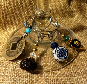 Chinese character wine charms; second from the left is a TIbetan bead blessed by the Monk